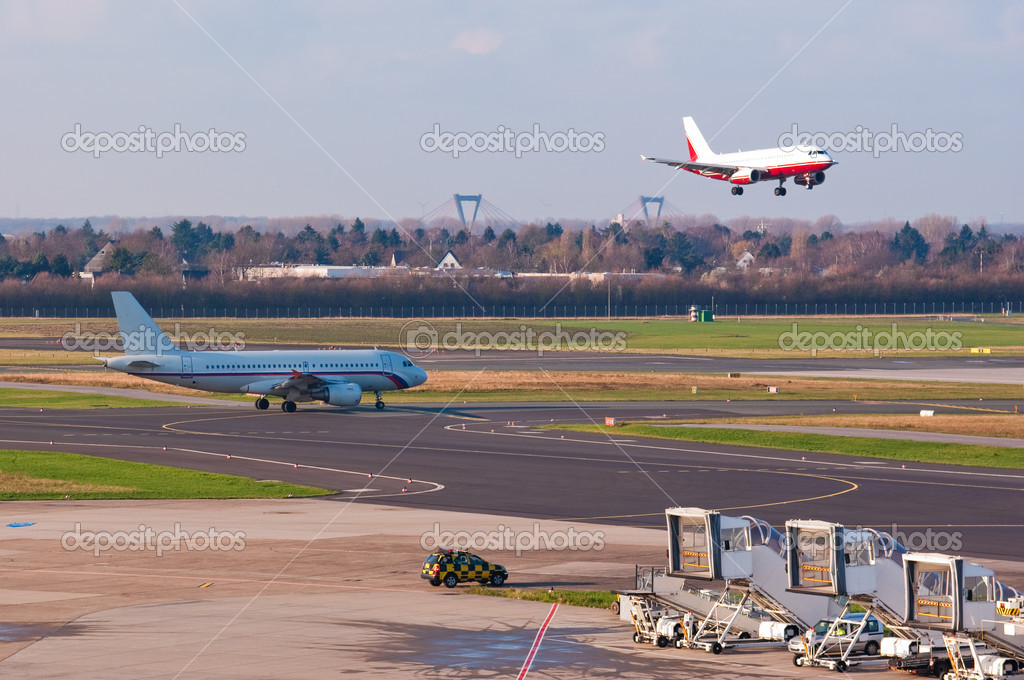 An airplane approaches to land while another one prepare for taking off  Stock Photo #2988969