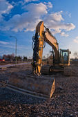 Yellow excavator and blue sky — Stock Photo