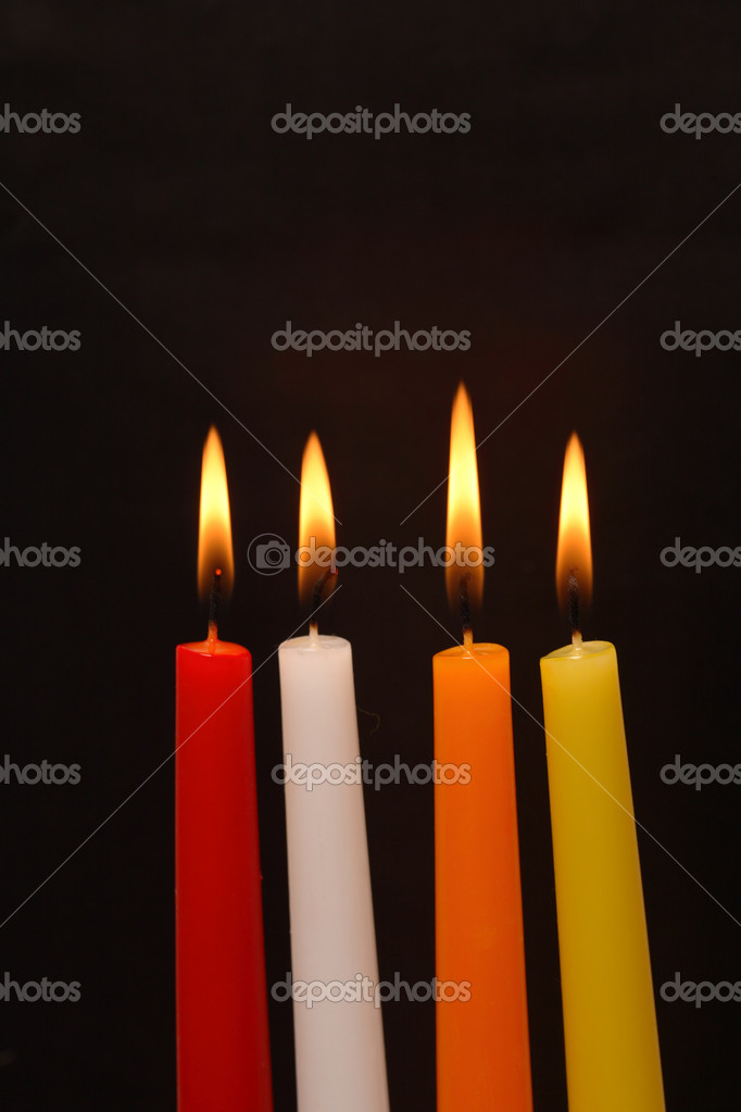 Set of four colored lighting candles on dark background — Stock Photo #3787968