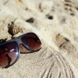 Modern sunglasses on sand - Stock fotografie