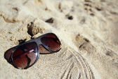 Modern sunglasses on sand — Stock Photo