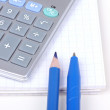 Calculator, pencil and pen on paper notebook — Stock Photo #3489089