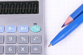 Calculator, pen and pencil on sheet of paper — Stock Photo