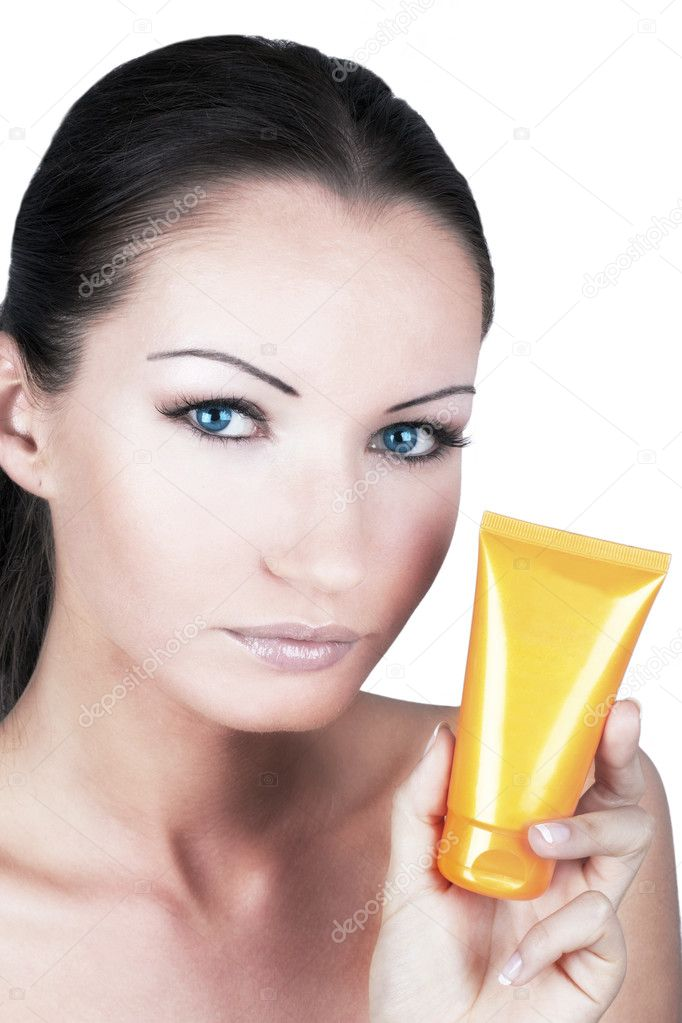 Tanned woman with sun protection cream in her hand — Stock Photo #3499763