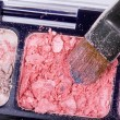 Make-up brush on crumbled orange eyeshadows - Stockfoto