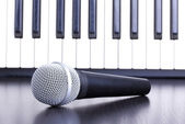 Microphone and piano keyboard — Stock Photo