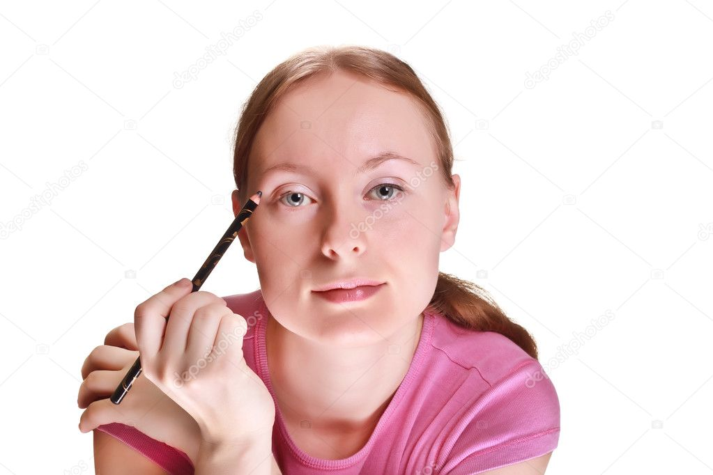She paints a black eye pencil on a white background  Stock Photo #2961718
