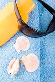 Havlu, güneş gözlüğü ve losyon — Stok fotoğraf