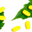 Yellow vitamin pills over green leaves — Stock Photo #3286262