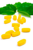 Yellow vitamin pills over green leaves — Stock Photo