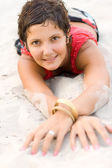 Brunet woman in red lying on a sand — Stock Photo
