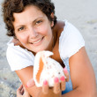 Woman on seacoast with a cockleshell in hands — Stock Photo