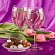 Glasses of  wine, flowers and sweets — Stock Photo