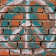 Brick wall with a symbol graffiti. - Stock Photo