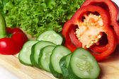 Pepper, salad and cucumber on a board close up. — Stock Photo