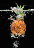 Small pineapple falling in water — Stock Photo