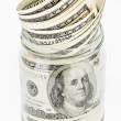 Many 100 US dollars in a glass jar — Stock Photo #3213879
