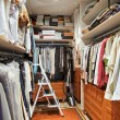 Wardrobe with many clothes and step-ladder — Stock Photo #3514834