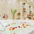 Modern bathroom in warm tones with jacuzzi and rose petals wide angle view — Stock Photo