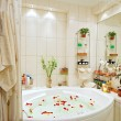 Royalty-Free Stock Photo: Modern bathroom in warm tones with jacuzzi and rose petals wide angle view