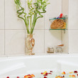 Part of bathroom with rose petals floating in water — Stock Photo