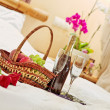 Roses, fruits basket and wine glasses on tea-tray in the bed — Stock Photo