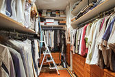 Wardrobe with many clothes and step-ladder — Stock Photo