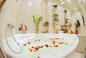 Bagno moderno in toni caldi con idromassaggio e ampio angolo di visualizzazione di petali di rosa — Foto Stock