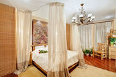 Medieval style bedroom with canopy bed on wide angle view — Stock Photo