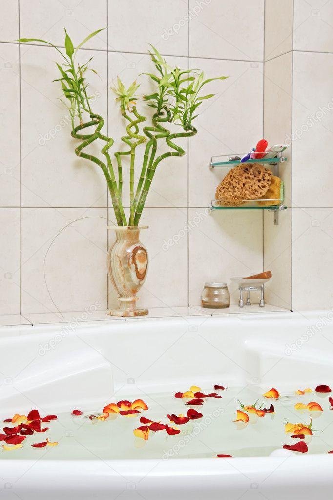 Part of bathroom with rose petals floating in water — Stock Photo #3514842