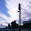 Semaphore on railway station in front of dramatic fleecy clouds — Stock Photo