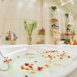 Modern bathroom in warm tones with jacuzzi and rose petals — Stock Photo #3543279