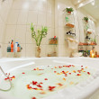 Modern bathroom in warm tones with jacuzzi and rose petals — Stock Photo