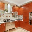 Kitchen interior with wooden furniture and build in utensils - Zdjcie stockowe