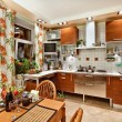 Kitchen interior with wooden furniture, table and many utensils - Stock Photo