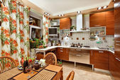 Kitchen interior with wooden furniture, table and many utensils — Foto de Stock