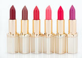 Multicolored color lipsticks arranged in line isolated on white — Stock Photo