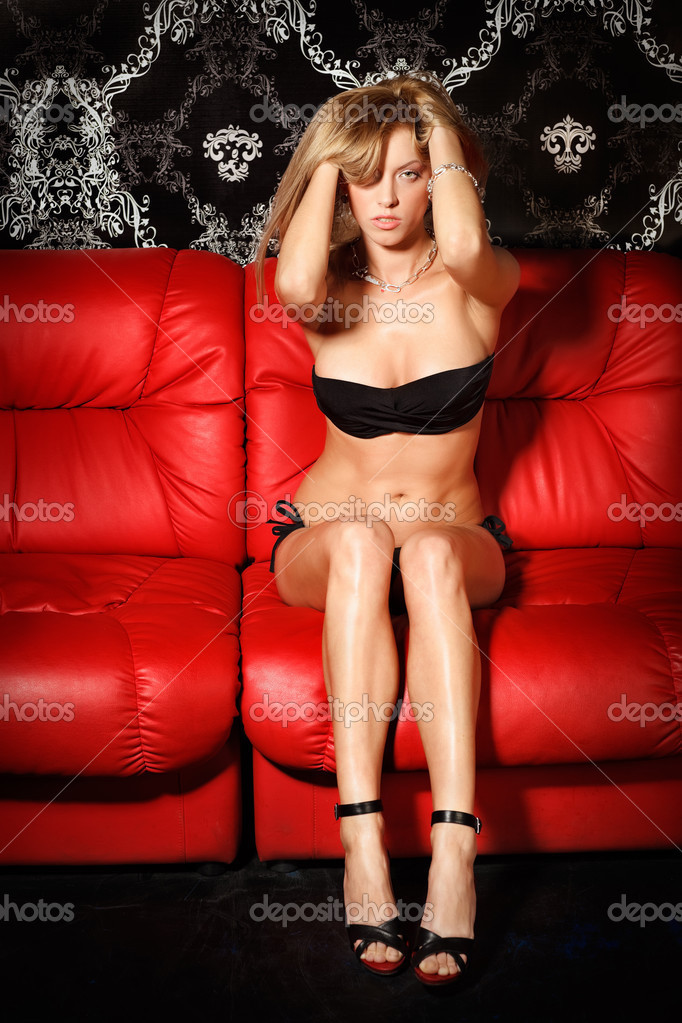 Sexy young blonde lady in black lingerie on red sofa  Stock Photo #3674526