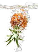 Small pineapple falling in water on white — Stock Photo