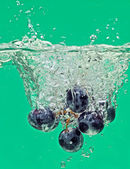 Bunch of grapes floating in water with air bubbles — Stock Photo