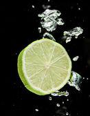 Lime (lemon) falling in water on black — Stock Photo