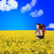 Happy backpackers in flowers field — Stock Photo