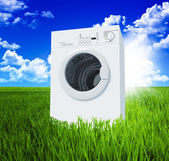 Washing machine and green field — Stock Photo