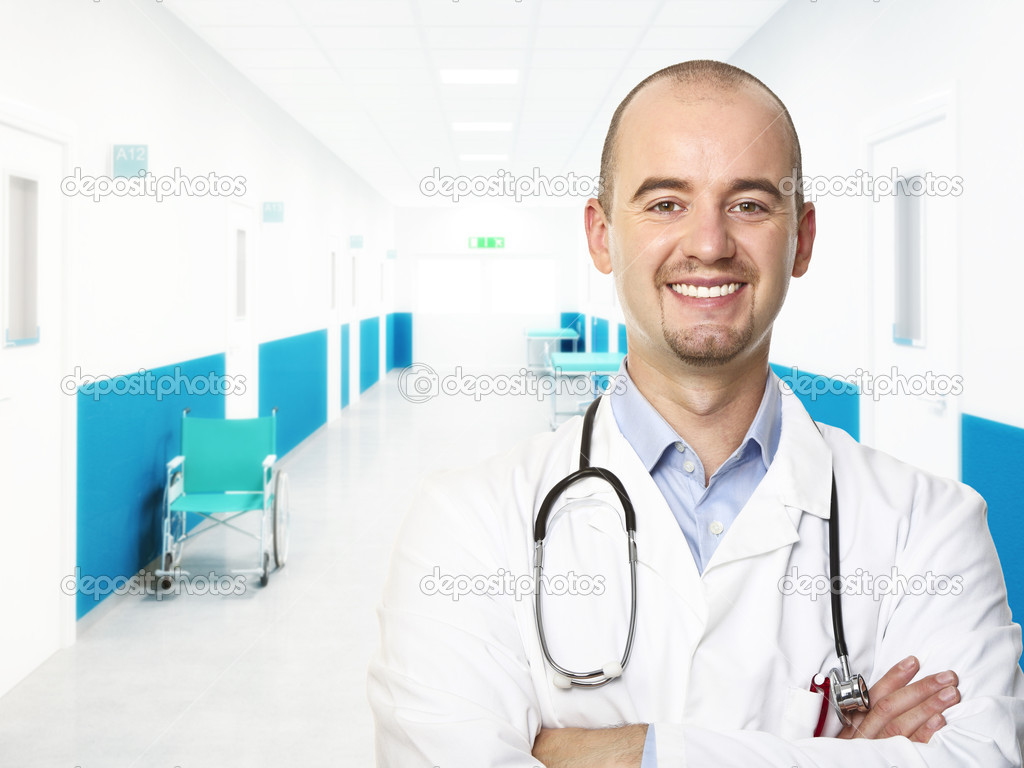 Young smiling doctor in aisle hospital background — Stock Photo #3528874