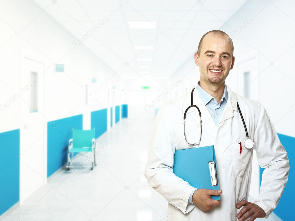 Smiling young doctor in aisle hospital background — Lizenzfreies Foto #3528887