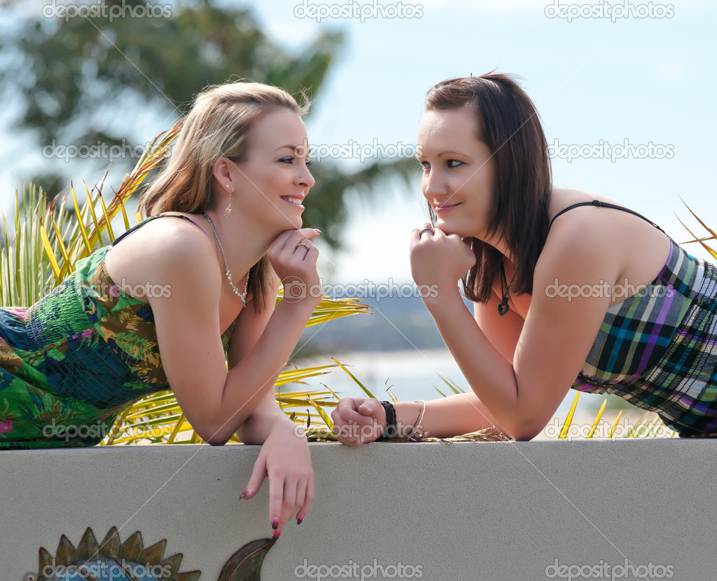 Two pretty young women laying along a wall — Stock Photo #3846605