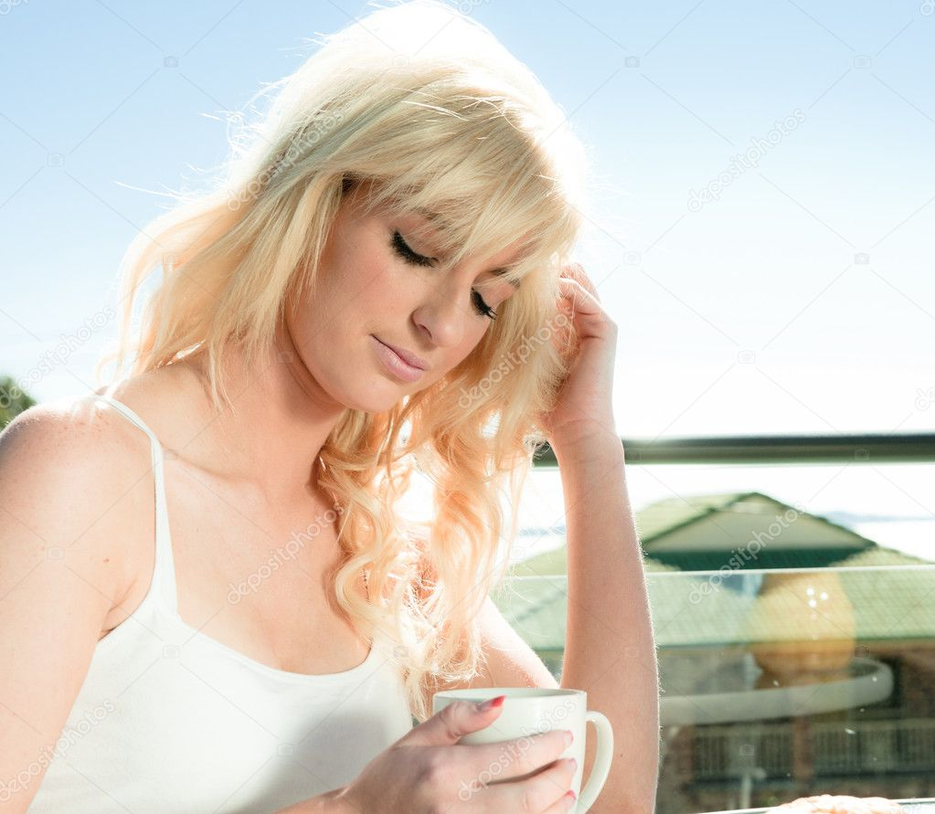 Beautiful blonde woman having coffee in a restaurant — Stock Photo #3860733