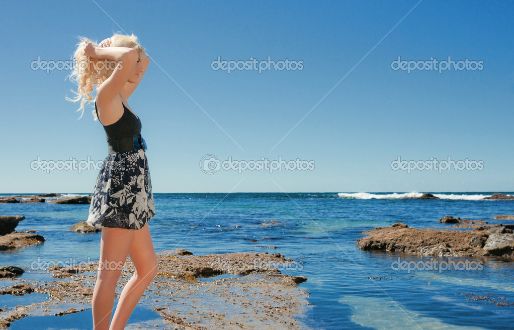 Beautiful young woman on the reef rocks at the sea — Stock Photo #3860754