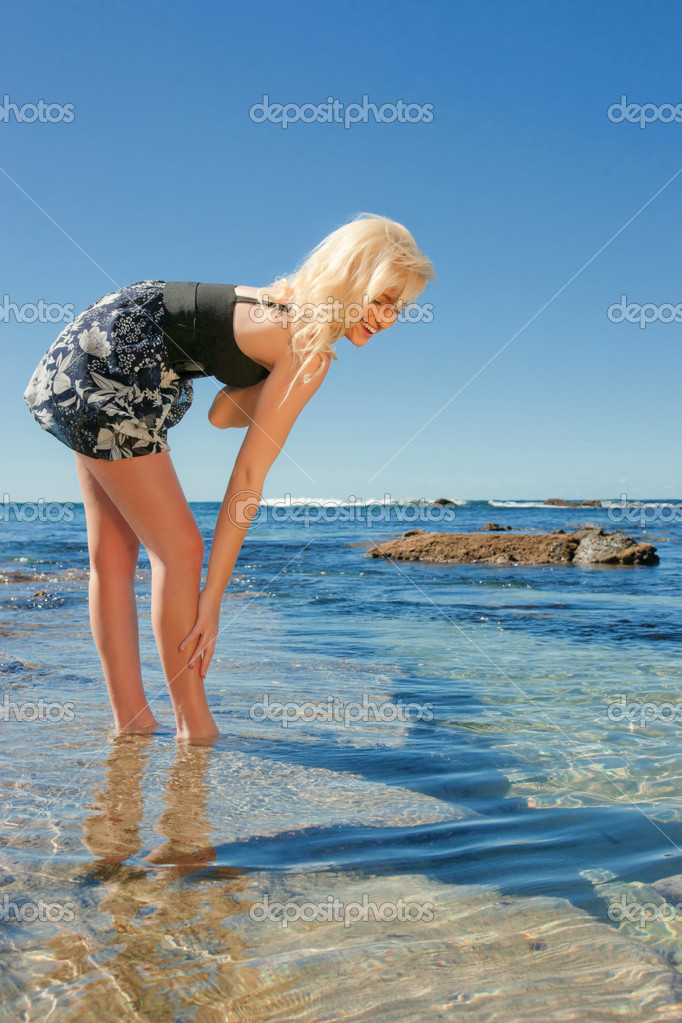 Beautiful young woman on the reef rocks at the sea — Stock Photo #3860757