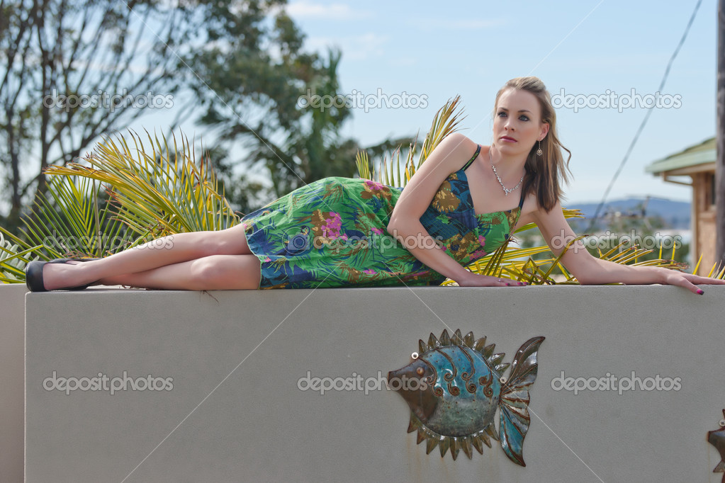 Pretty young woman laying along a wall — Stock Photo #3885009